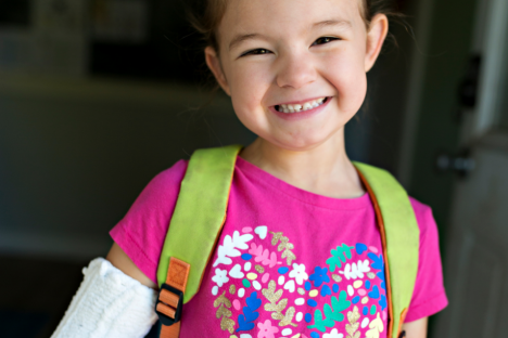 child smiling with an arm cast